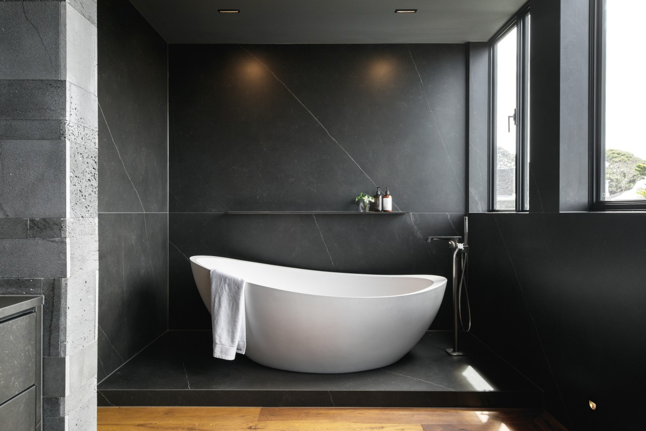 The freestanding bath sits on a pedestal floor