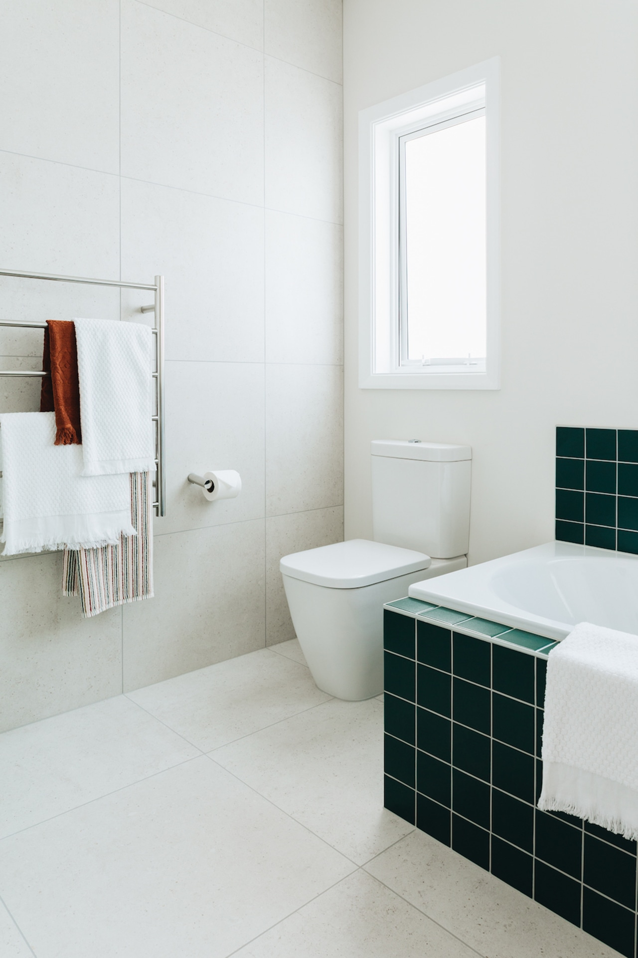 Large format white wall and floor tiles provide