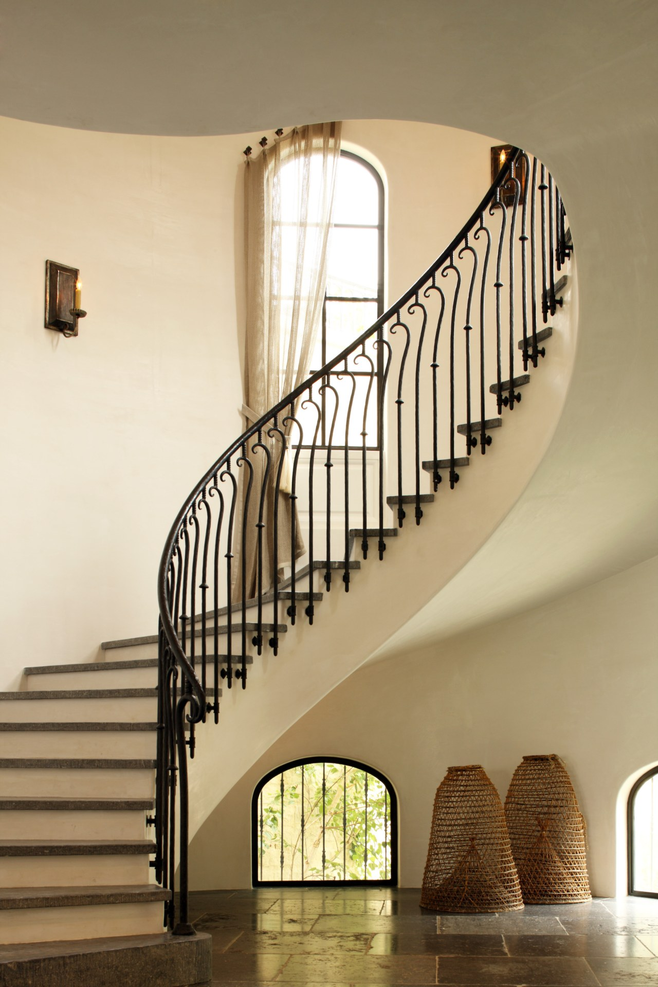 This graceful staircase, lined with bespoke wrought iron