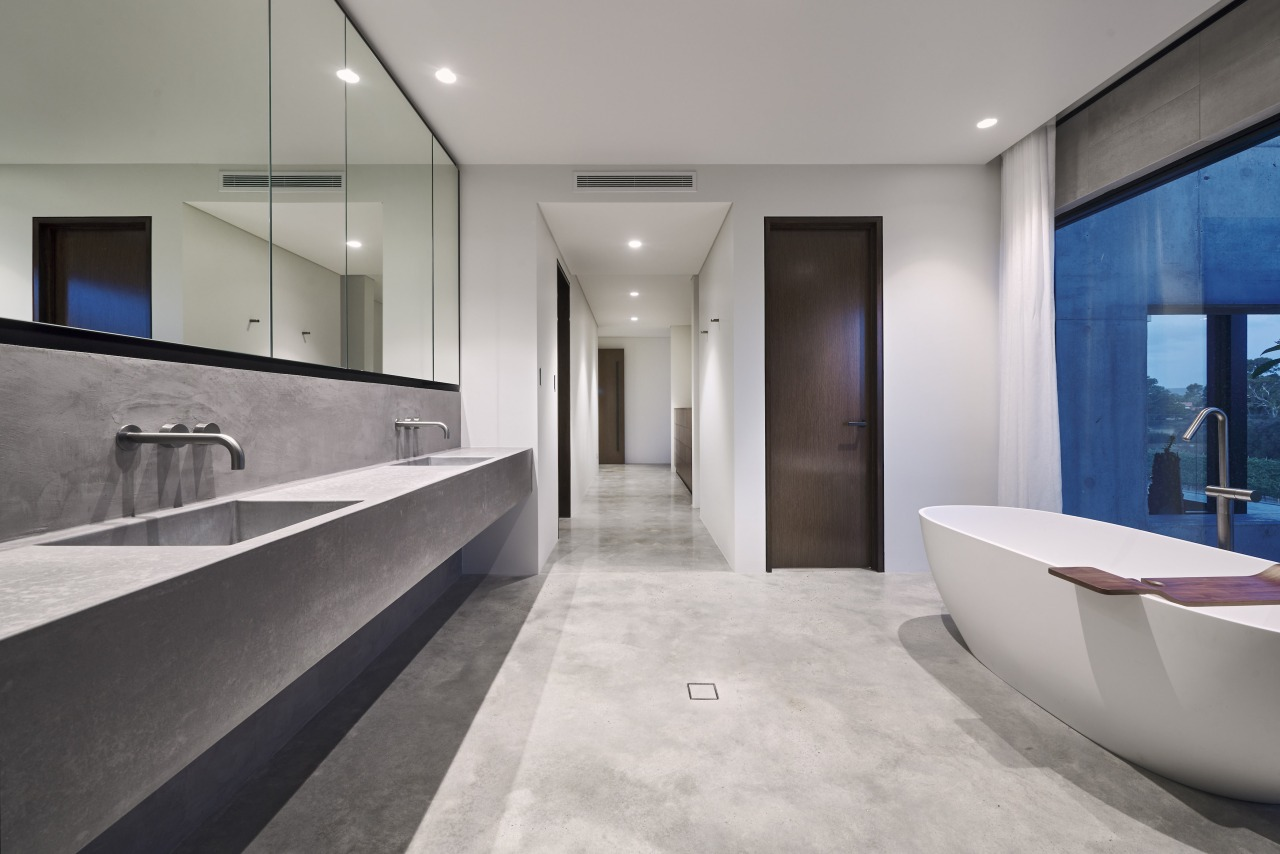 An expansive concrete vanity with formed basins runs