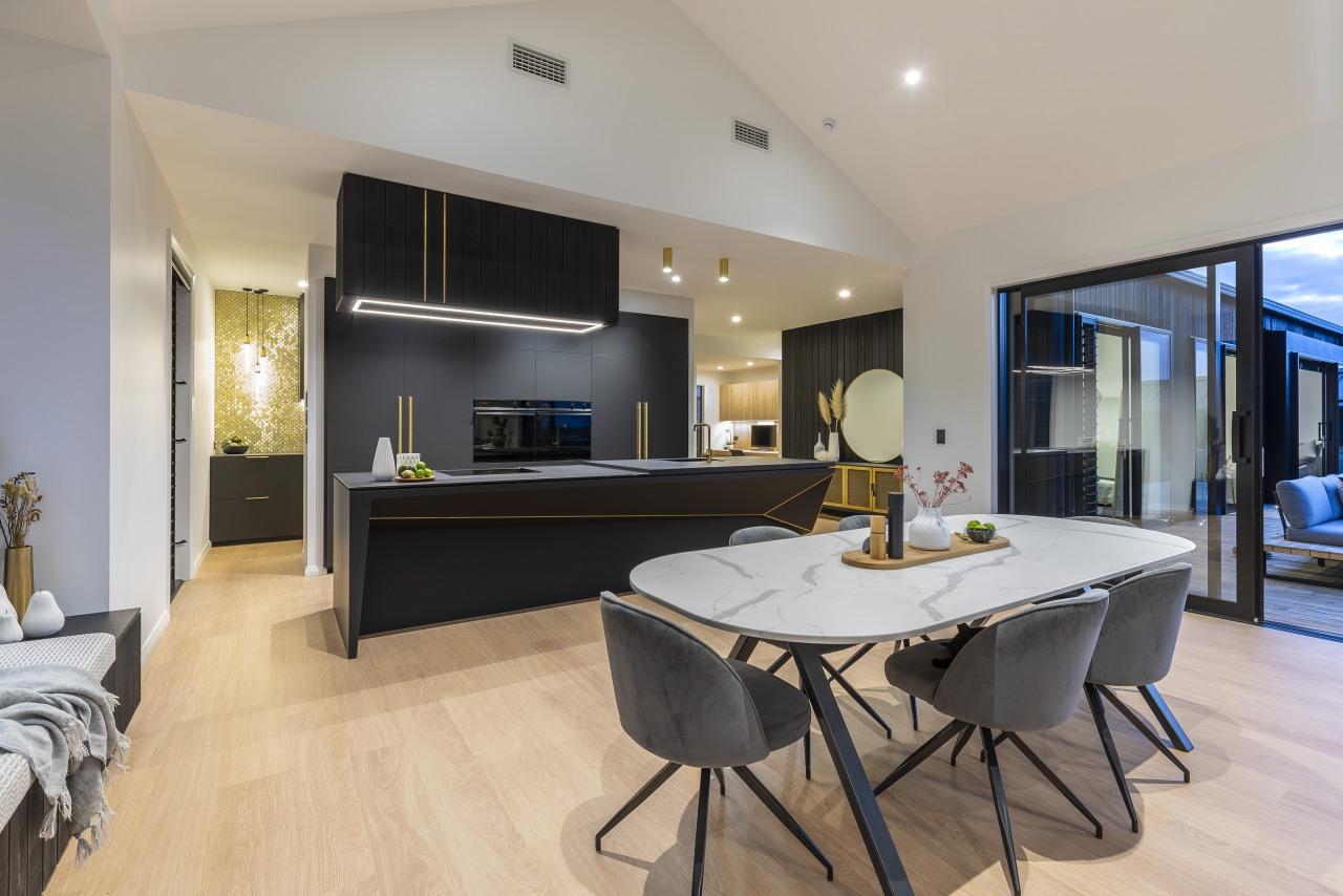 The kitchen features soft black matt cabinetry, brass