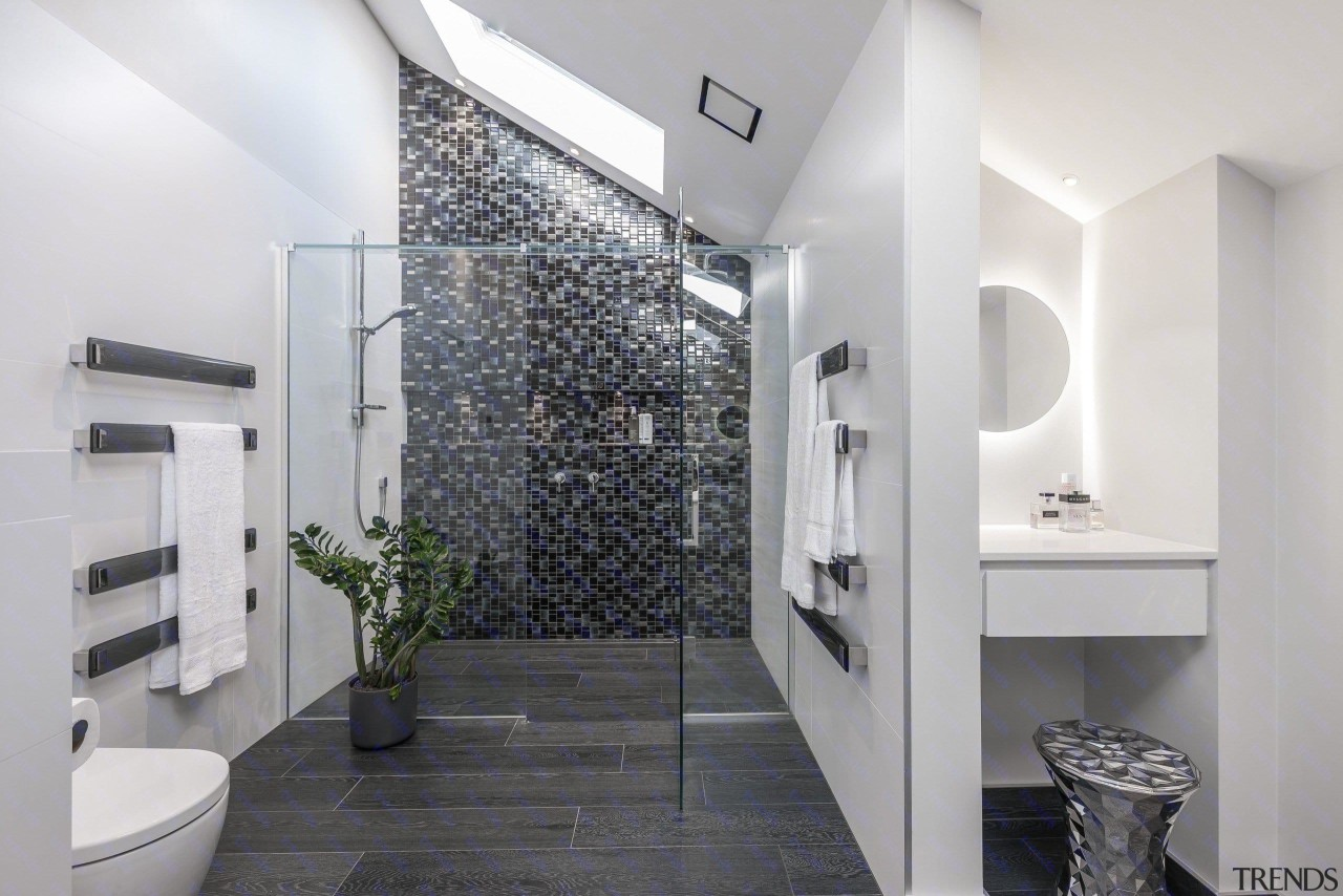 This bathroom features an excellent example of a architecture, bathroom, floor, home, interior design, property, real estate, room, tile, wall, gray, white