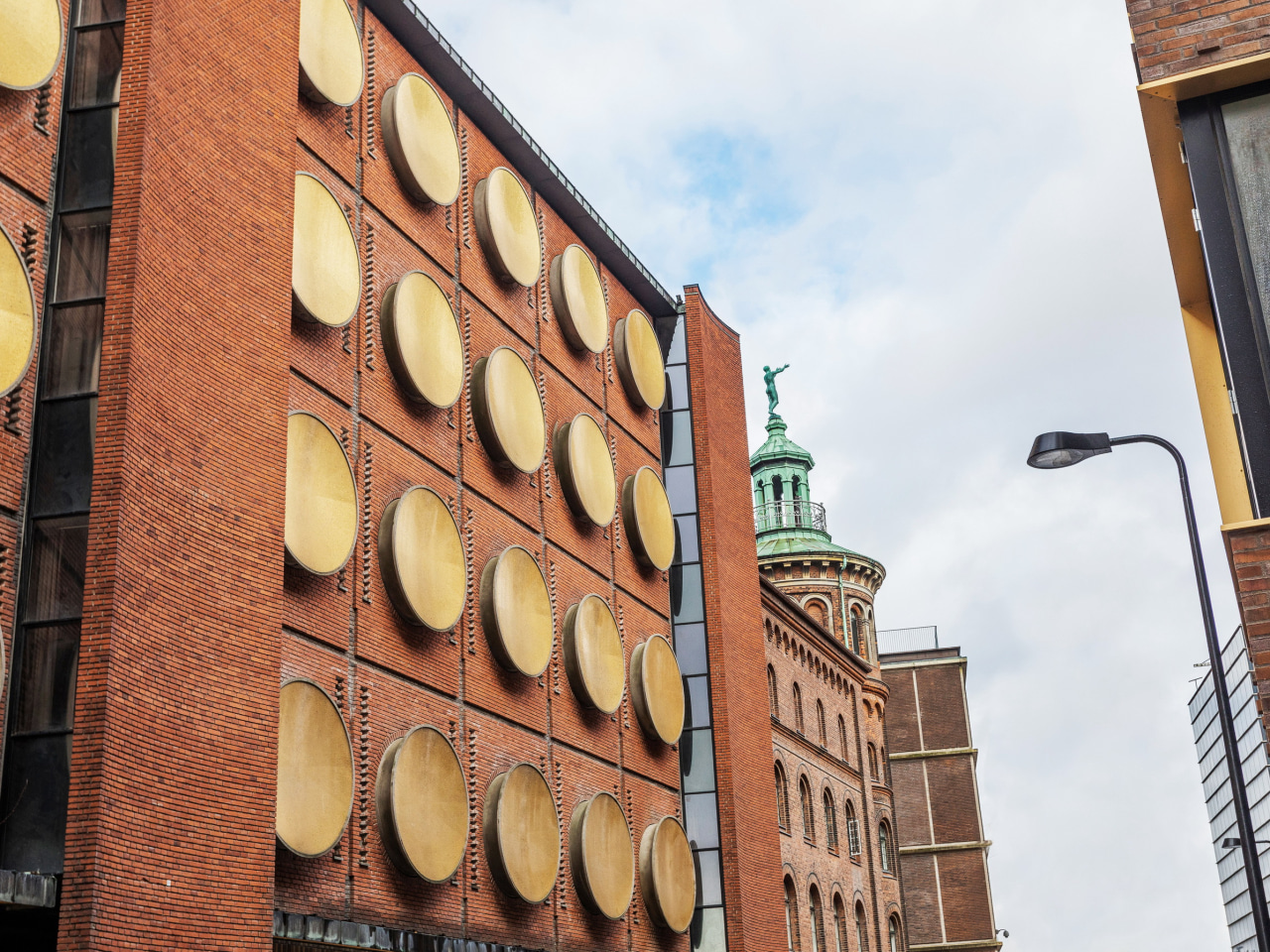 Adorning the shell of the building are over architecture, brick, brickwork, building, city, downtown, facade, iron, metropolitan area, neighbourhood, signage, sky, street, town, urban area, wall, white, orange