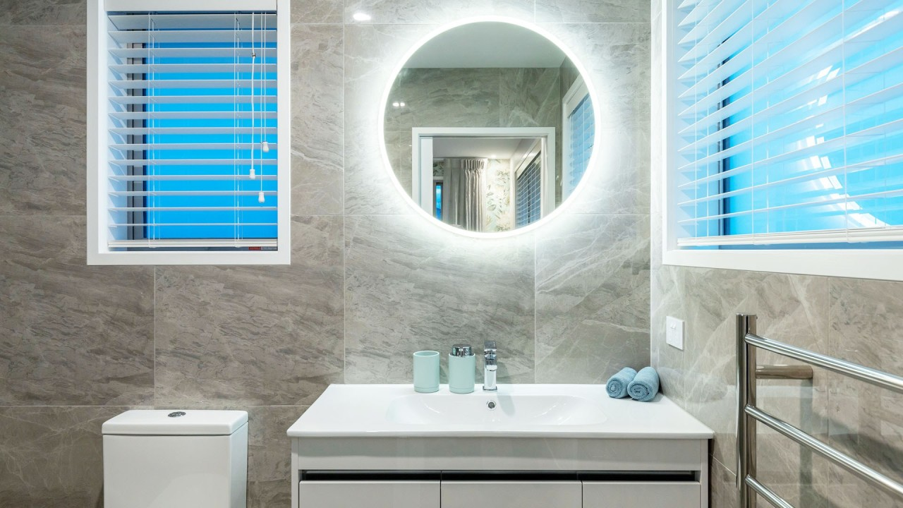 A modern vanity, feature tiles and windows on