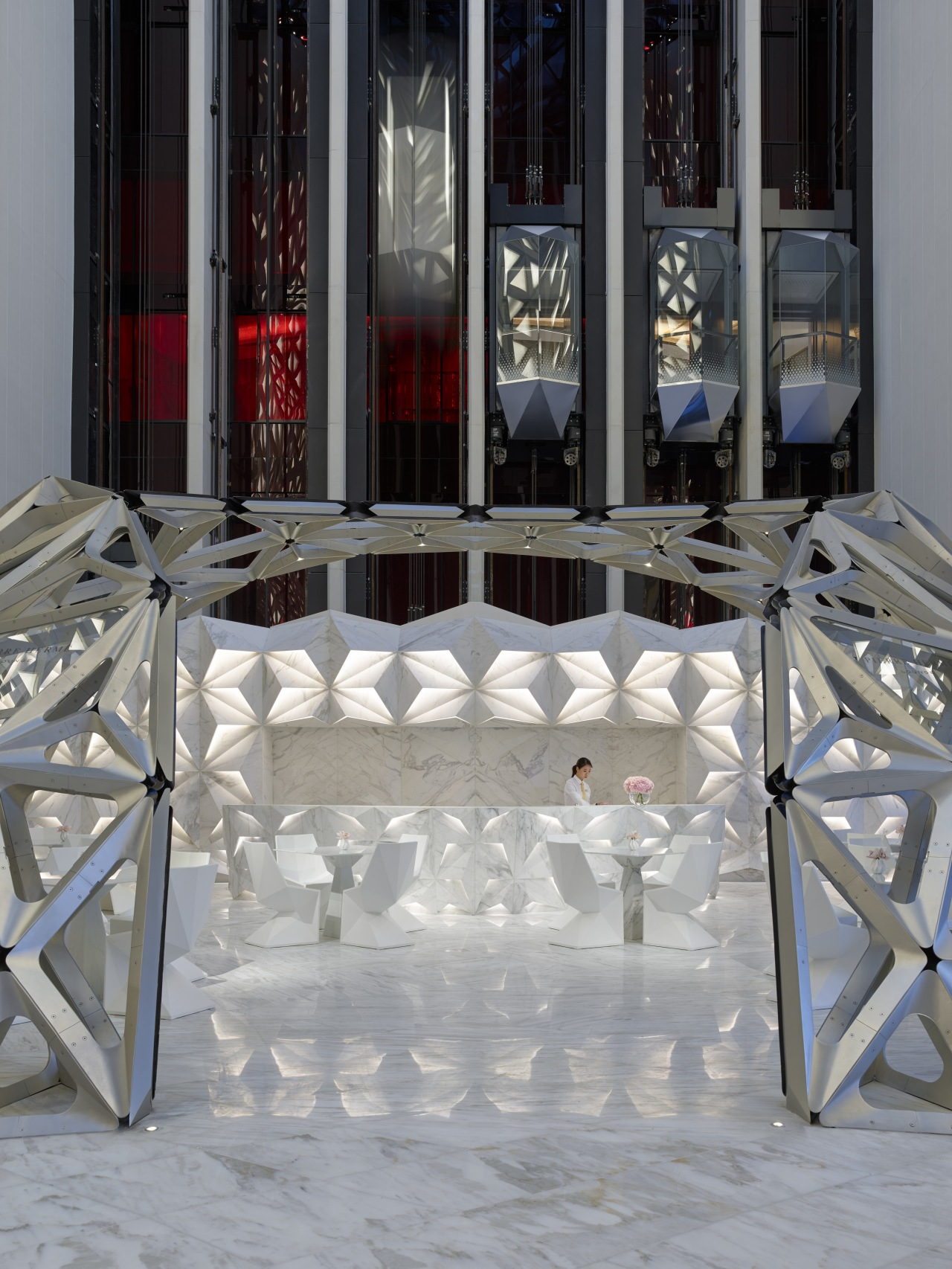 Glass elevators rise behind the faceted reception desk chair, floor, flooring, furniture, table, window, gray, black