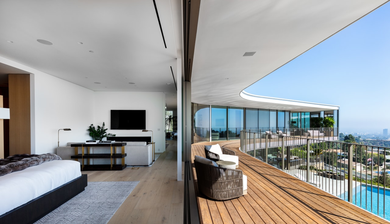 At one end of the first floor of architecture, balcony, building, wood floor, floor, flooring, deck, bedroom, furniture, home, house, interior design, living room, table, QPC