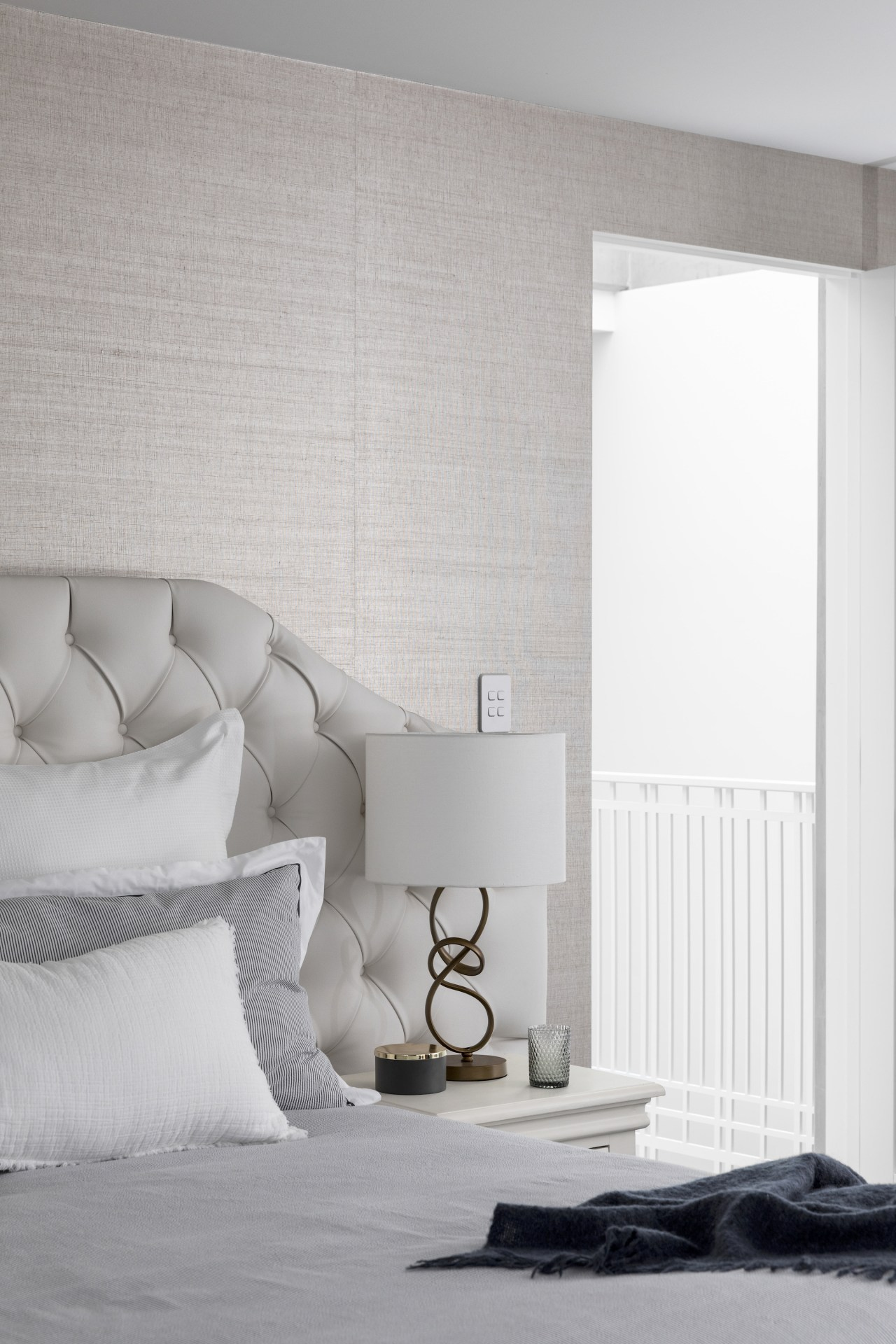 The layered and textured bedroom features a grass-cloth