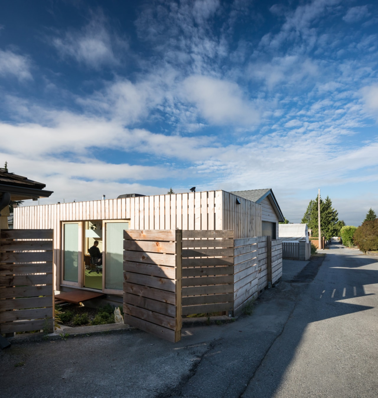 The Rba Office is unobtrusive within the street architecture, building, cloud, cottage, facade, home, house, property, real estate, residential area, roof, shed, siding, sky, wood, black