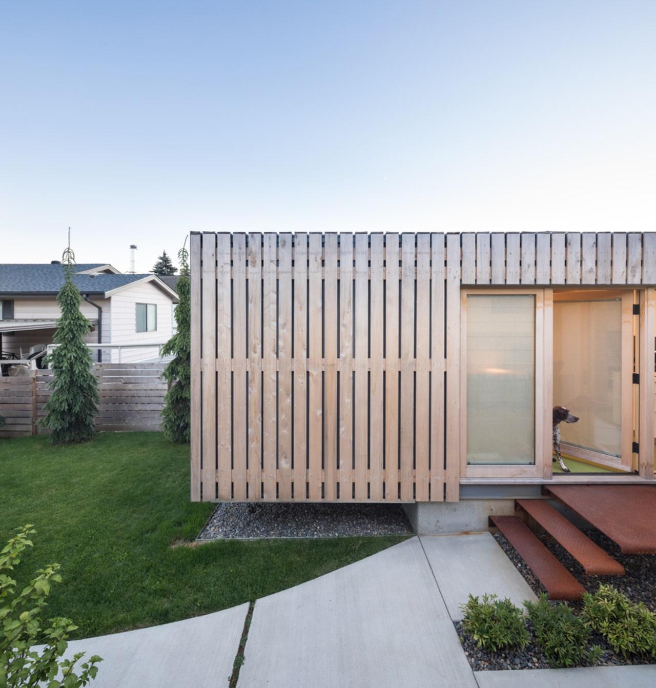 The over-sized corten steel shipping container has a architecture, backyard, daylighting, facade, home, house, property, real estate, residential area, shed, siding, white