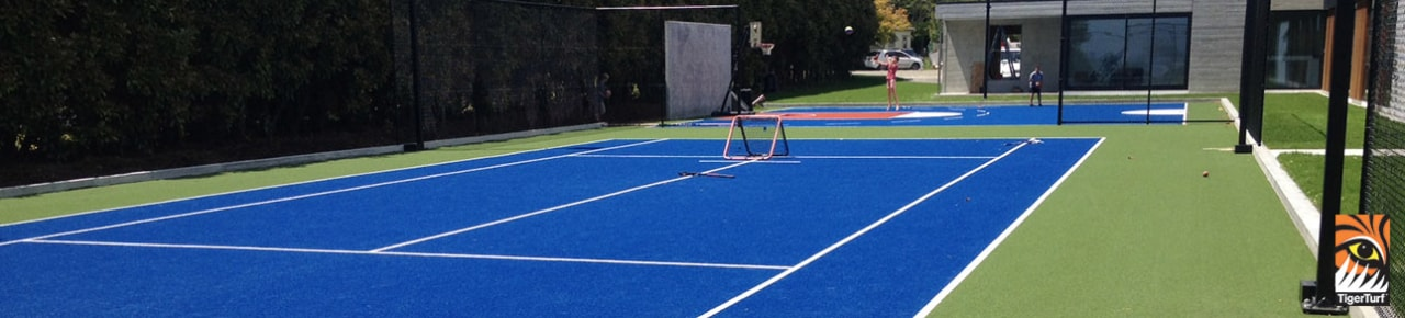 TigerTurf multi-sports surfaces are the product of many ball game, floor, grass, individual sports, leisure, net, play, racquet sport, sport venue, sports, tennis, tennis court, tennis player, blue, black