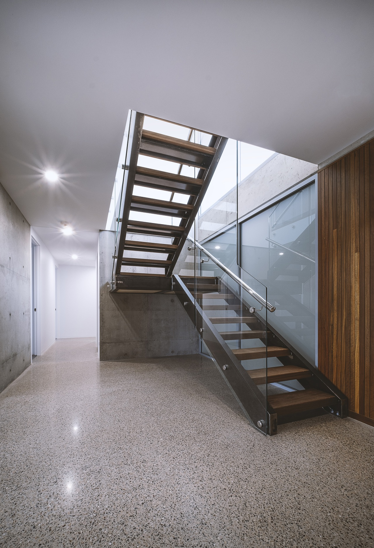A translucent glass wall sits beyond the stairs