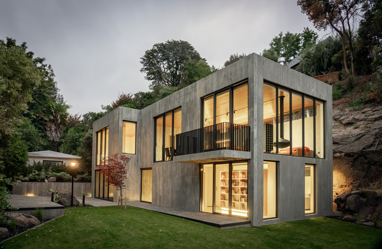 The concrete home with basalt cliff behind –