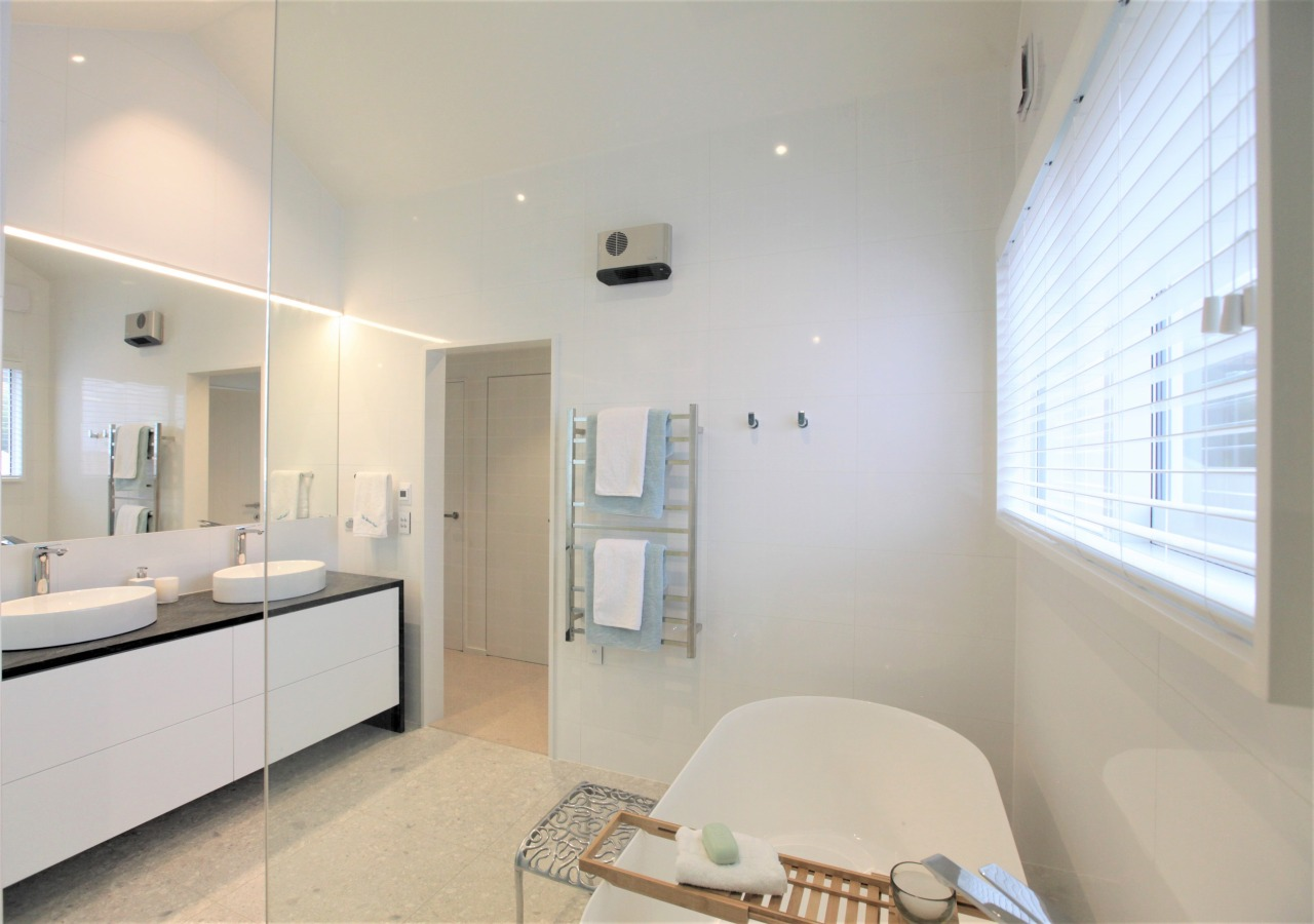 The bathroom's clear glass shower stall and high