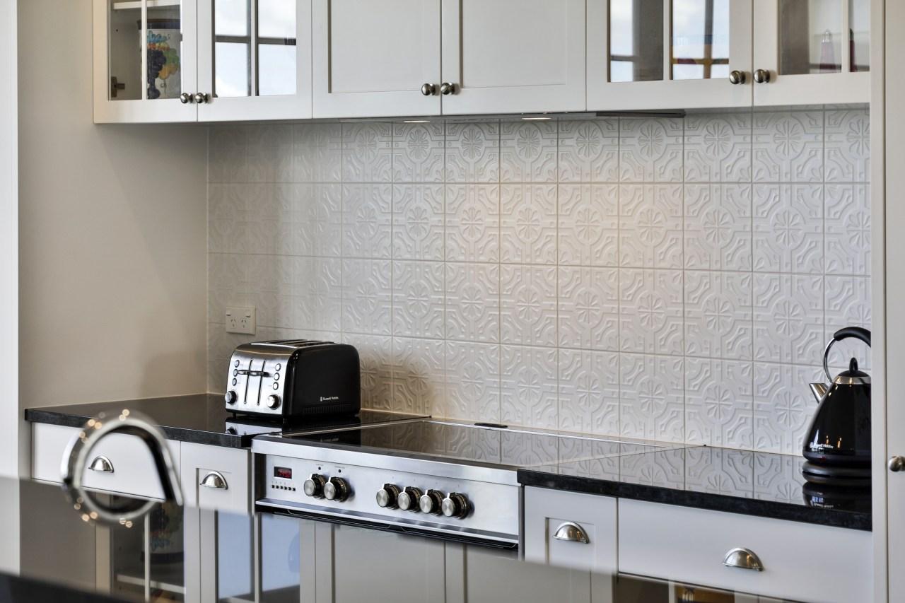 The elegant embossed tile splashback was also installed