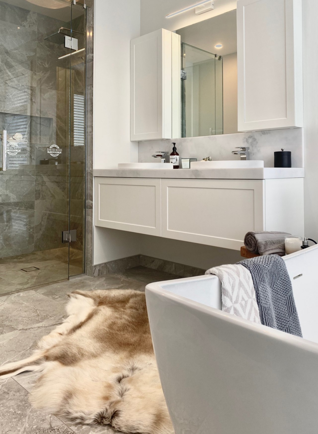 The vanity and wall cabinets have panelled fronts