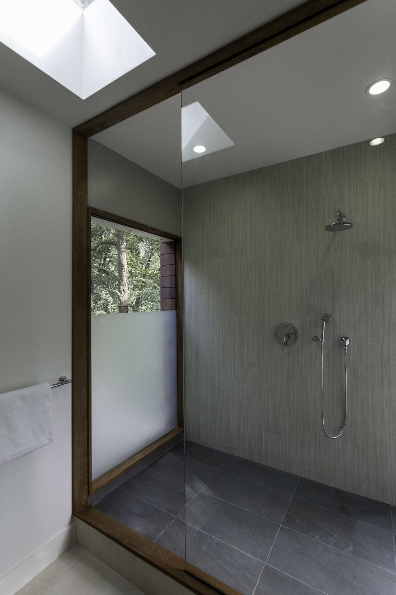A large shower has views out to the architecture, bathroom, ceiling, daylighting, floor, home, house, interior design, gray, black