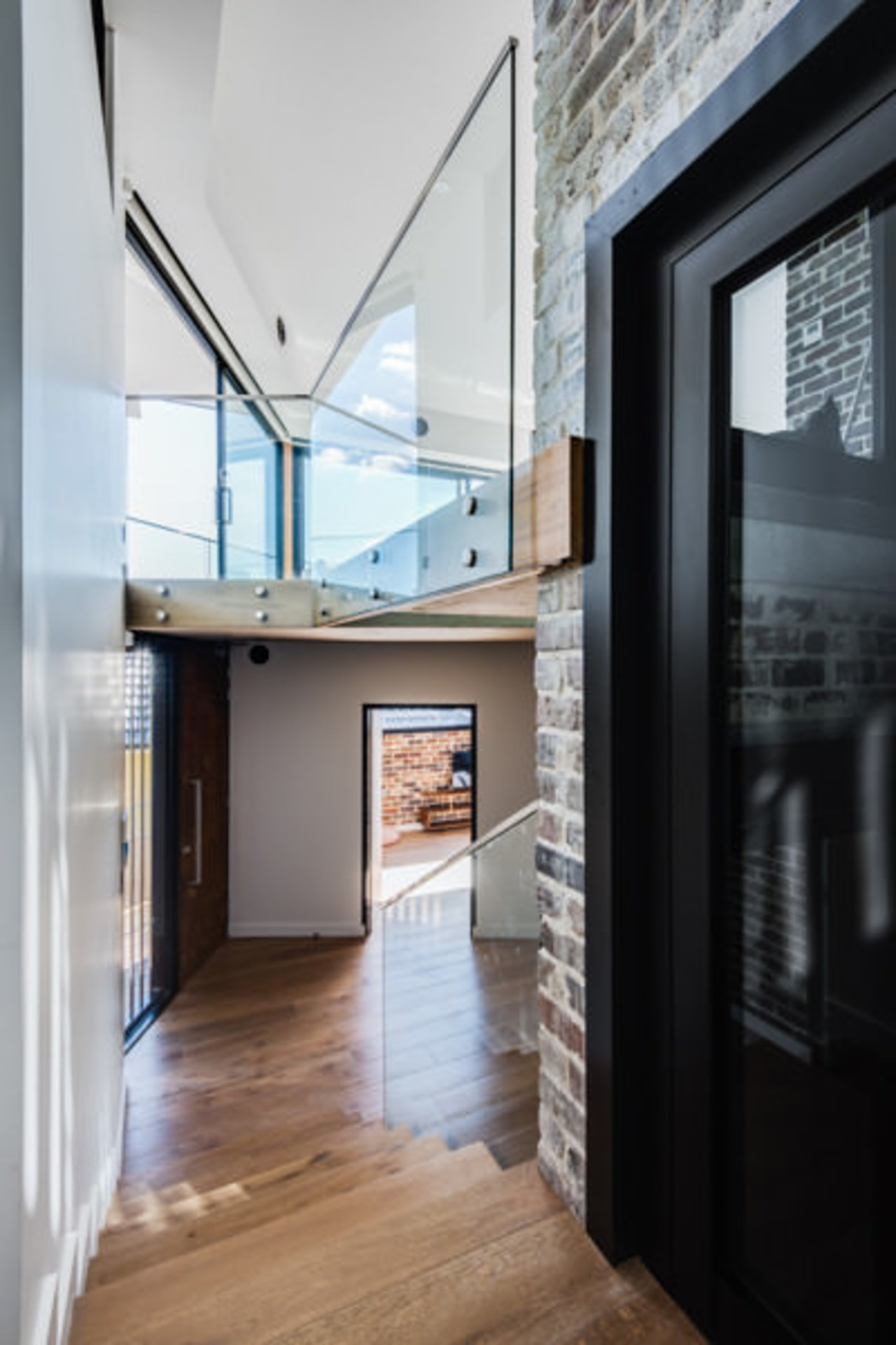 A glass balustrade allows light to flow throughout apartment, architecture, ceiling, daylighting, floor, flooring, hardwood, home, house, interior design, loft, real estate, window, wood flooring, gray, black