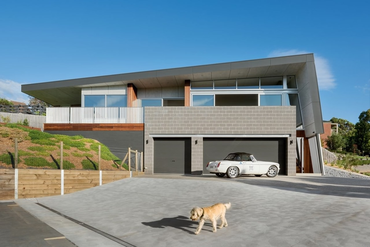 The street view of the home reveals the architecture, building, elevation, facade, home, house, luxury vehicle, property, real estate, residential area, gray, teal