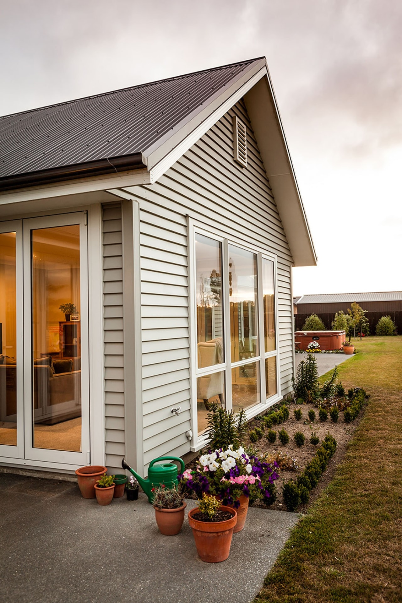 Built to last the test of time, this cottage, facade, home, house, real estate, residential area, shed, siding, window, white, brown