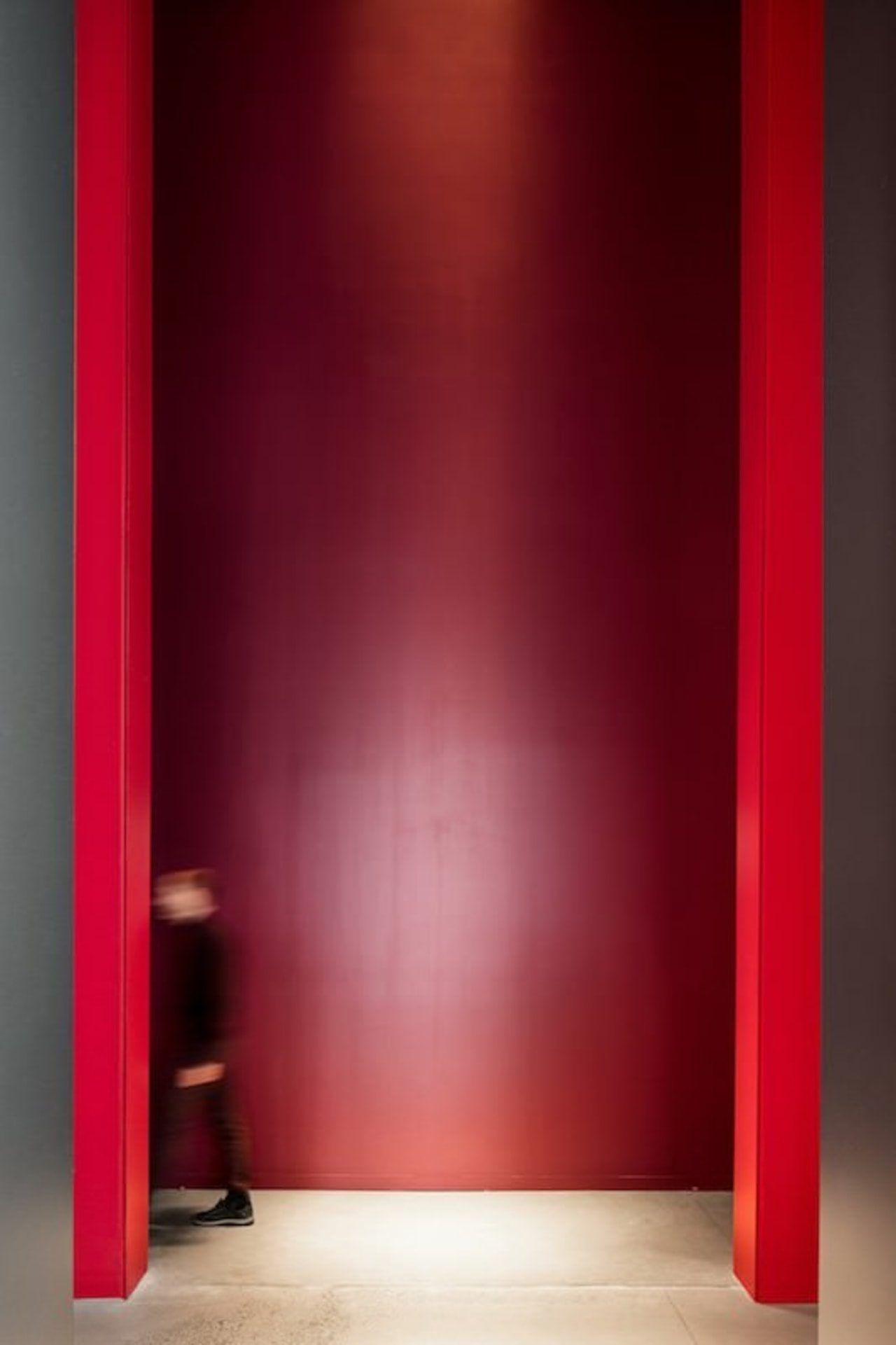 This massive doorway is certainly imposing door, floor, interior design, light, lighting, red, wall, red