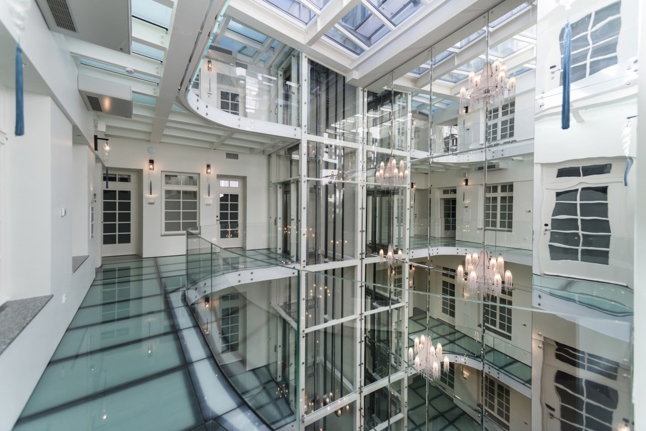 A large atrium features opaque glass floors apartment, building, condominium, daylighting, glass, property, real estate, window, gray