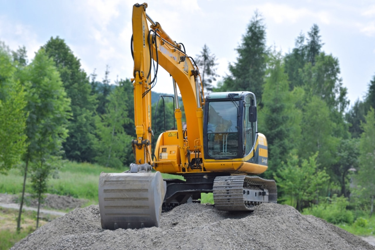 Is it possible to build a home in asphalt, bulldozer, construction equipment, tree, vehicle, green, white