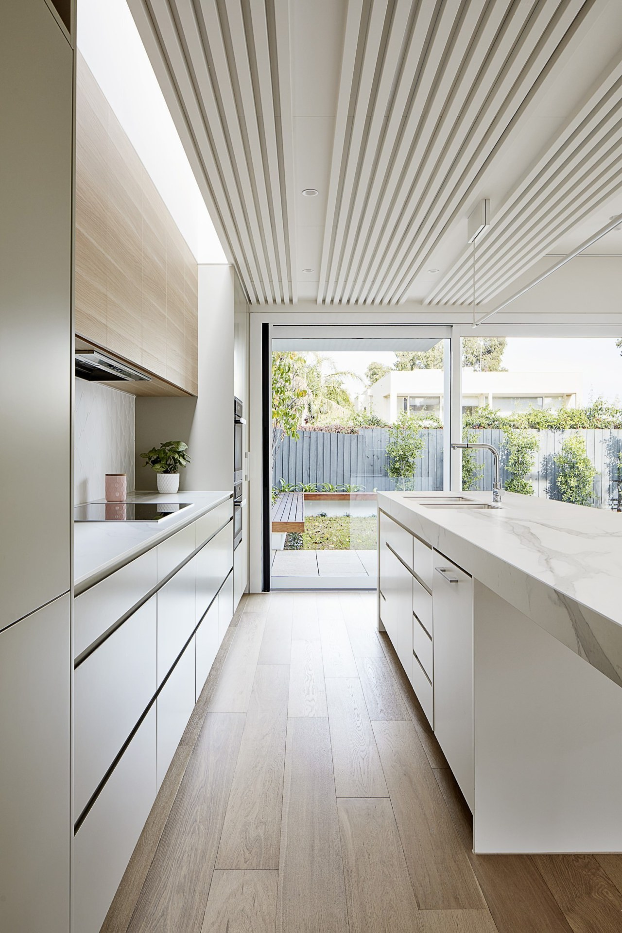 The kitchen opens right out onto the backyard architecture, ceiling, countertop, daylighting, floor, house, interior design, kitchen, real estate, window, gray, white