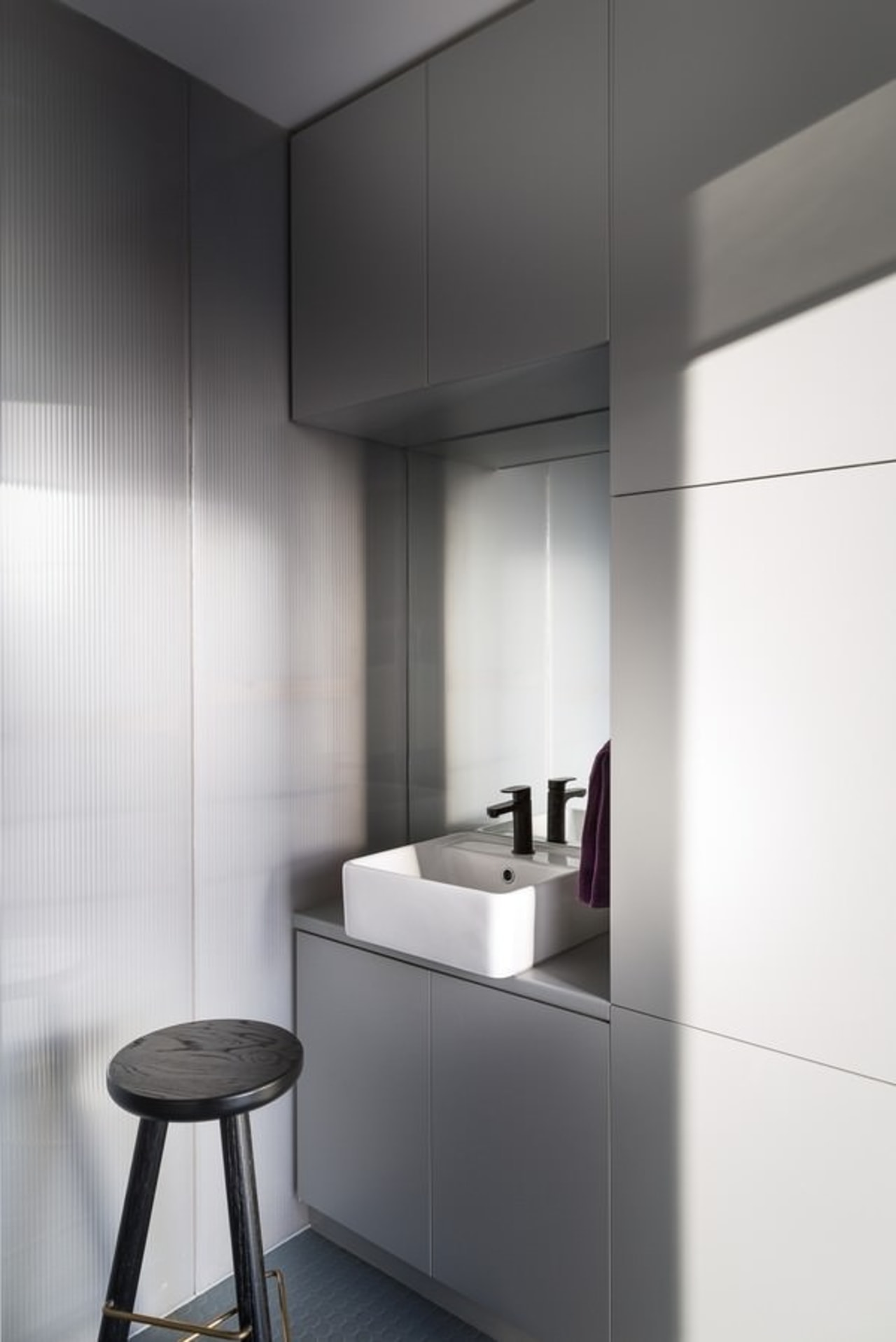 This tiny bathroom is distinctly modern and features floor, interior design, product design, tap, white, gray