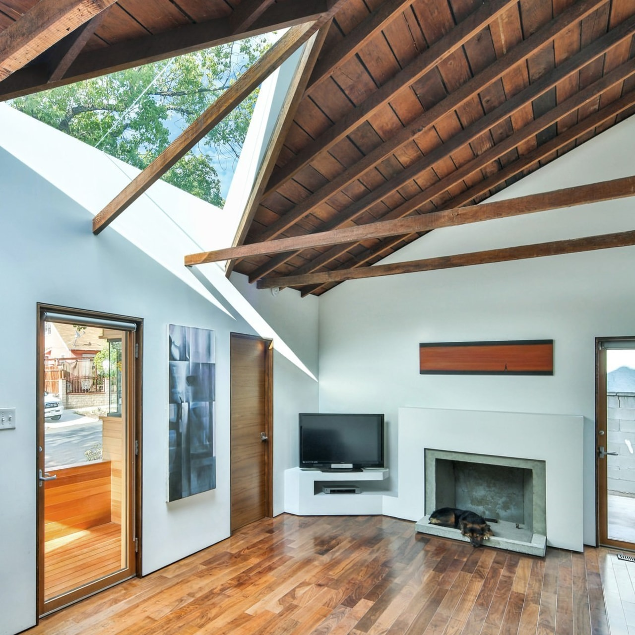 This triangular window lights up the living room architecture, beam, ceiling, daylighting, floor, hardwood, home, house, interior design, laminate flooring, living room, real estate, roof, window, wood, wood flooring, white