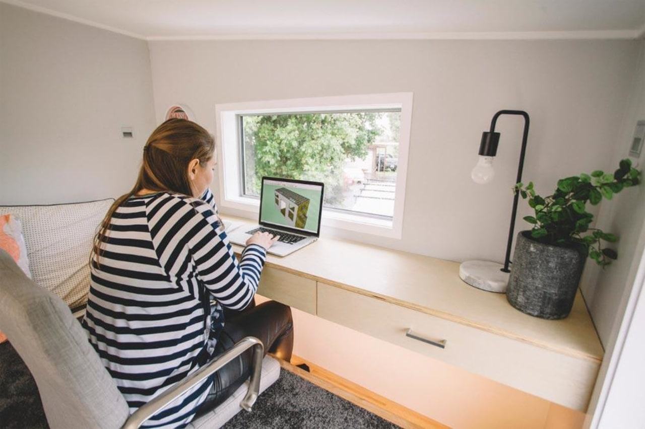 The Millennial by Build Tiny features a desk, floor, furniture, home, house, interior design, office, real estate, room, window, gray