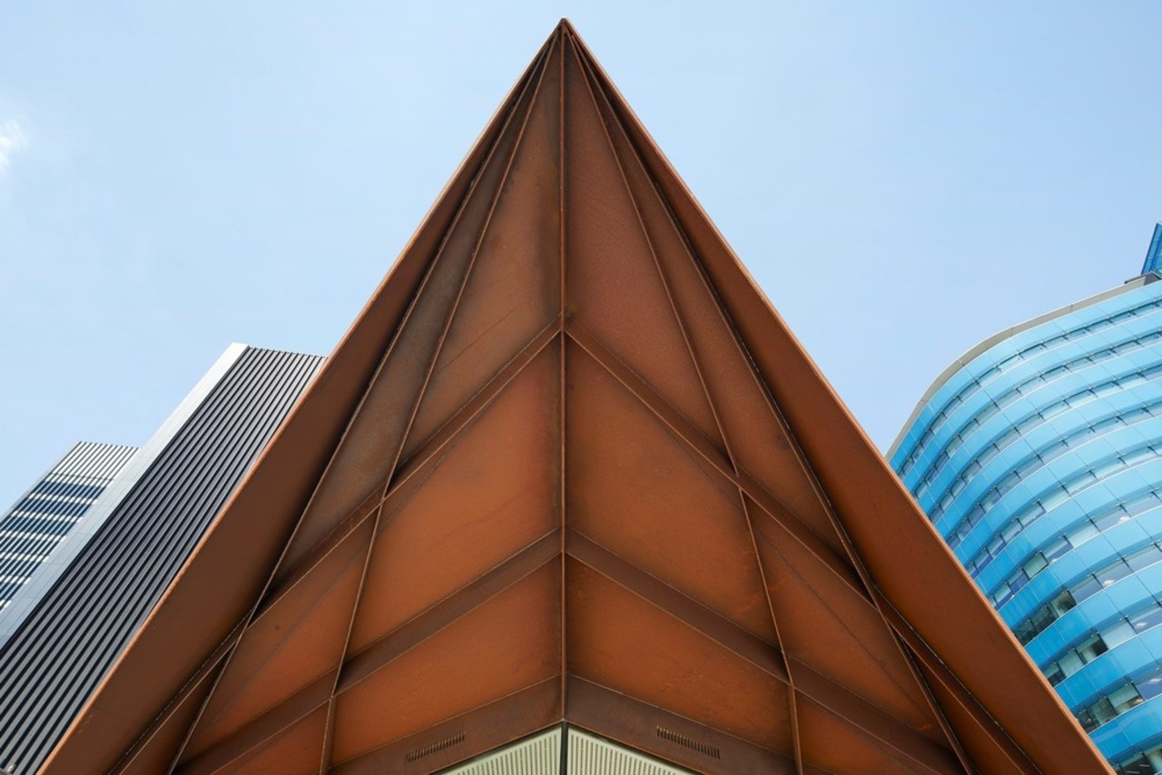The angles evoke the precedent of the City angle, architecture, building, commercial building, corporate headquarters, daylighting, daytime, facade, landmark, line, metropolitan area, roof, sky, skyscraper, structure, symmetry, tower block, teal, brown