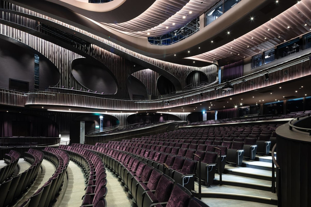 Conceived as a cultural sanctuary, the performance venue architecture, audience, auditorium, building, ceiling, concert hall, convention center, heater, interior design, musical instrument accessory, opera house, orchestra pit, performing arts center, stage, theatre, black
