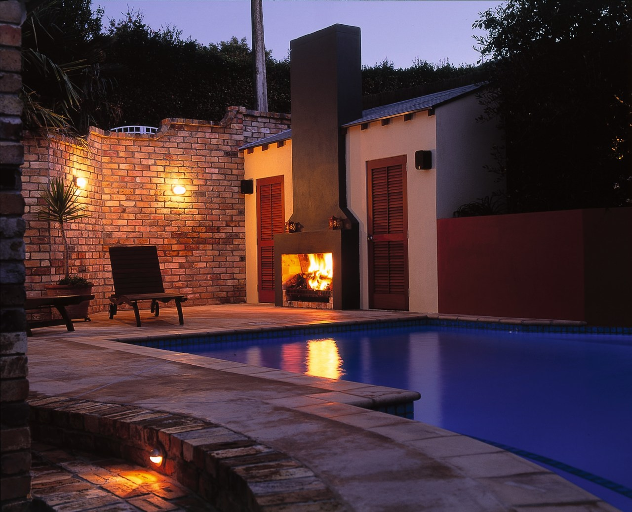 View of this pool backyard, estate, fireplace, home, house, landscape lighting, lighting, property, real estate, swimming pool, black