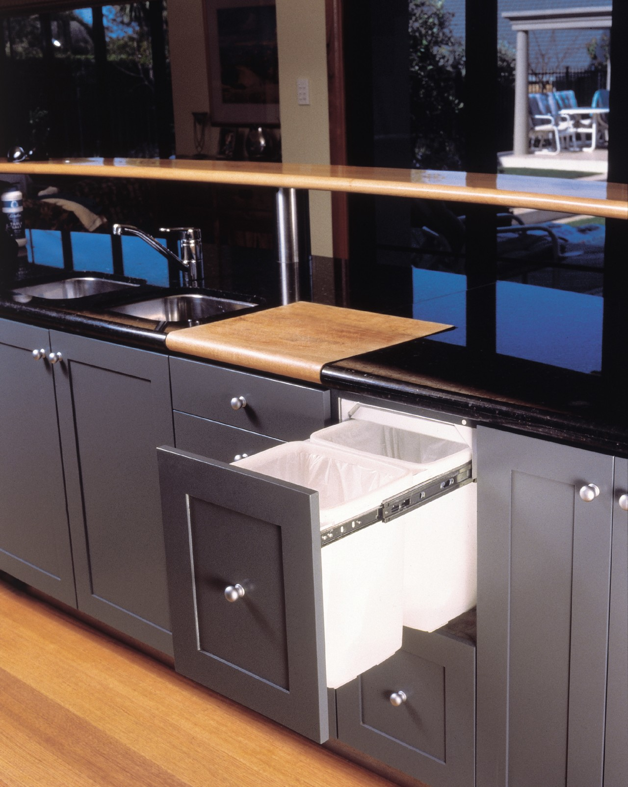 Examples of a tidy way to store rubbish cabinetry, countertop, furniture, kitchen, black, gray