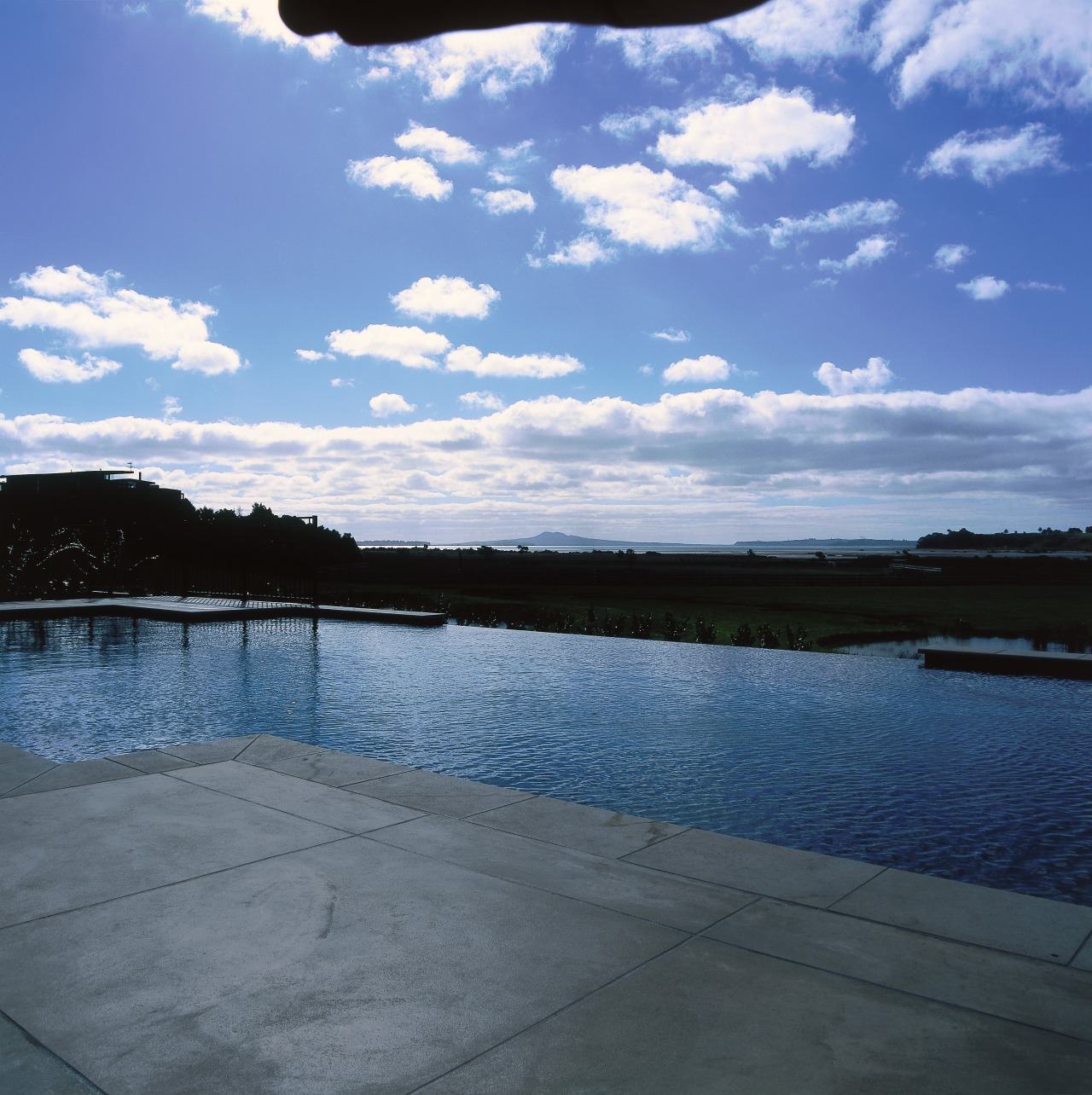 Infinity edge pool with sandstone coloured concrete surround calm, cloud, horizon, lake, loch, meteorological phenomenon, phenomenon, reflection, reservoir, river, sky, sunlight, tree, water, water resources, waterway, teal