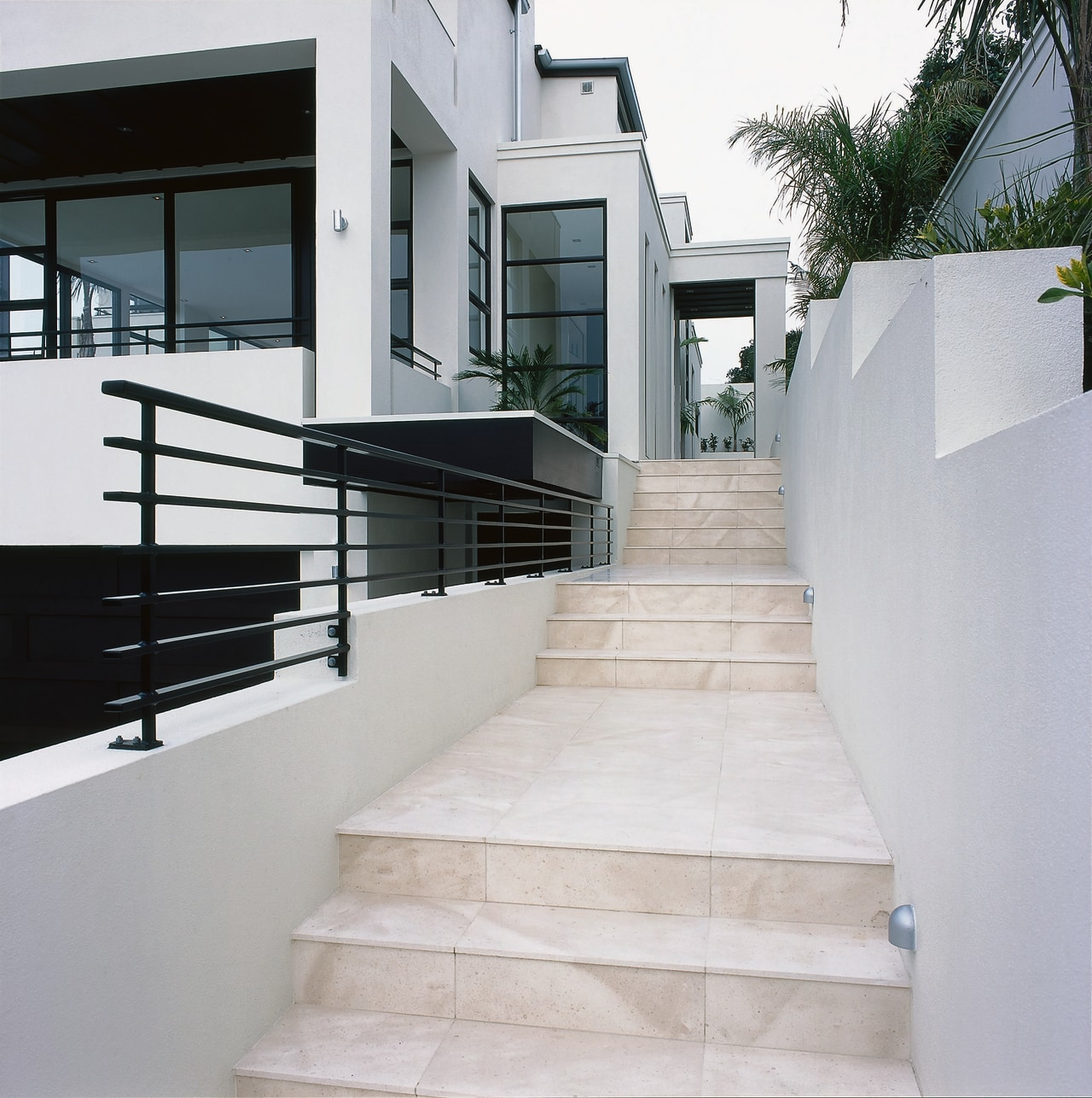 A stairway featuring coffee-coloured limestone tiles. The stairway apartment, architecture, handrail, home, house, stairs, gray