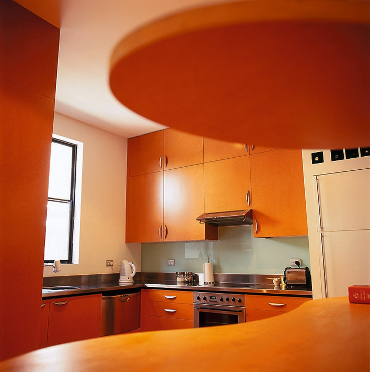 View of the modern kitchen architecture, cabinetry, ceiling, countertop, floor, flooring, hardwood, interior design, kitchen, light fixture, orange, room, table, wall, red, brown
