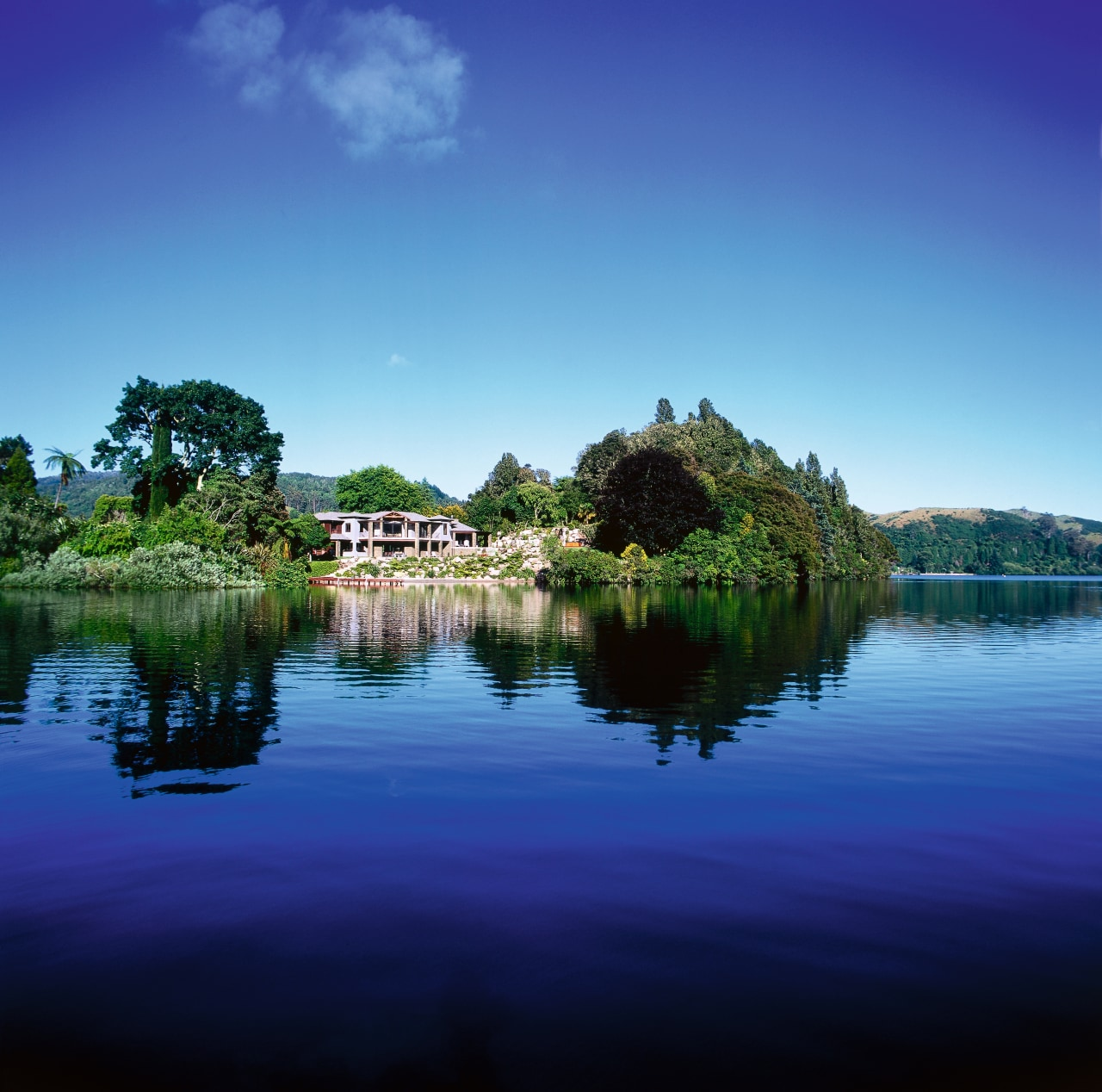 View of lakeside property. House is surrounded by atmosphere, bank, body of water, calm, cloud, daytime, grass, horizon, lake, landscape, loch, morning, nature, pond, reflection, reservoir, river, sky, tree, water, water resources, watercourse, waterway, wetland, blue, teal