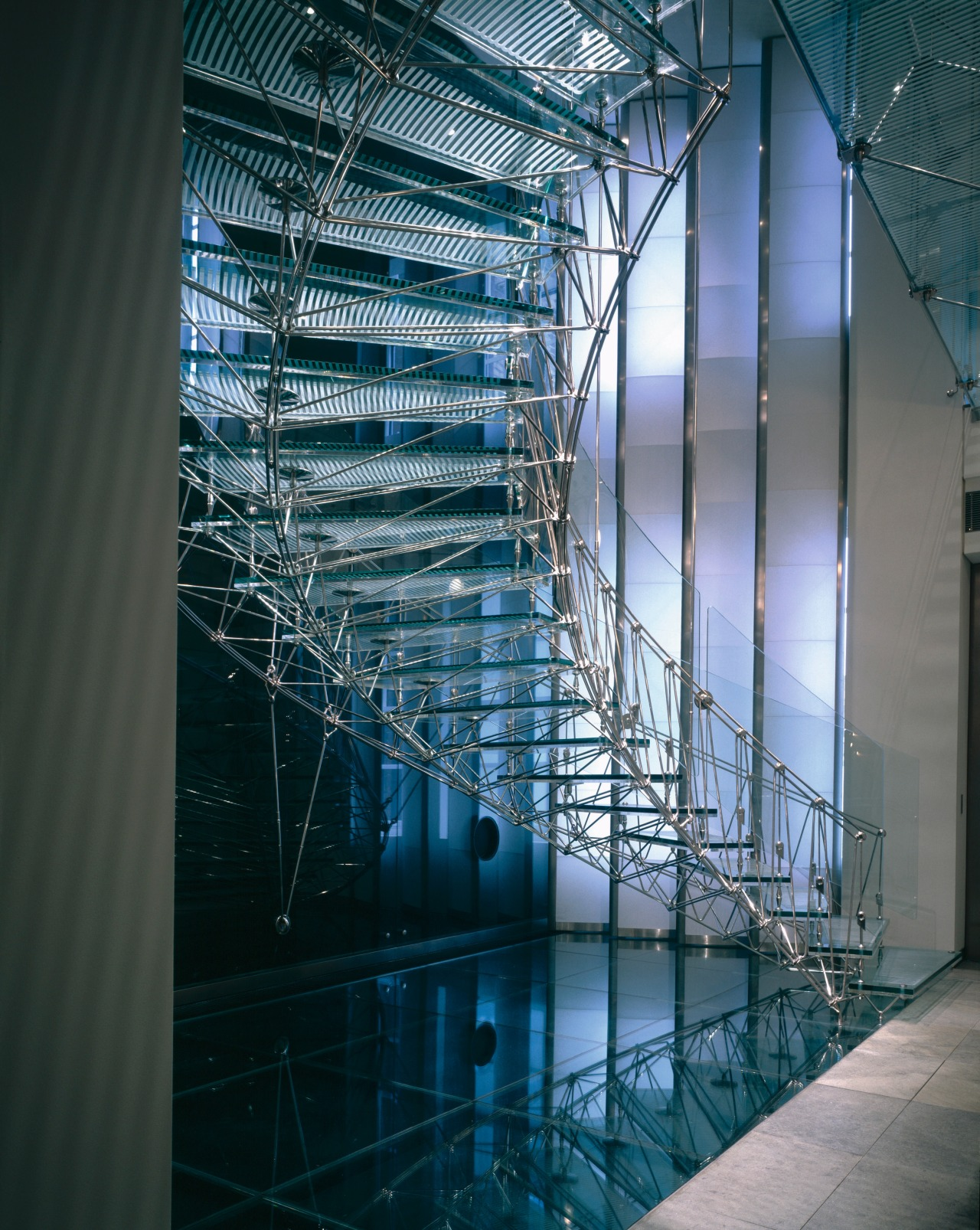 A view of the glass and metal stairway. architecture, building, daylighting, facade, glass, headquarters, line, metropolis, reflection, structure, teal, black