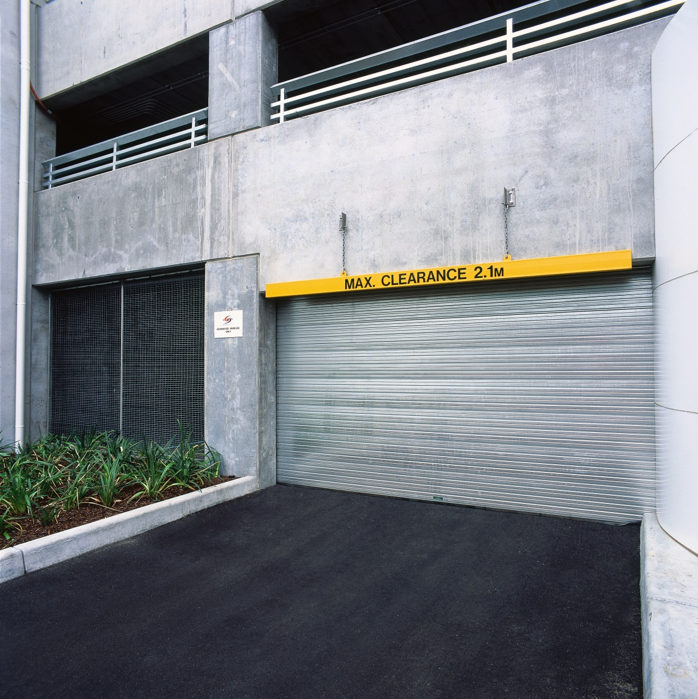 External view of galvanised steel sectional overhead door architecture, asphalt, building, door, facade, real estate, wall, white, black