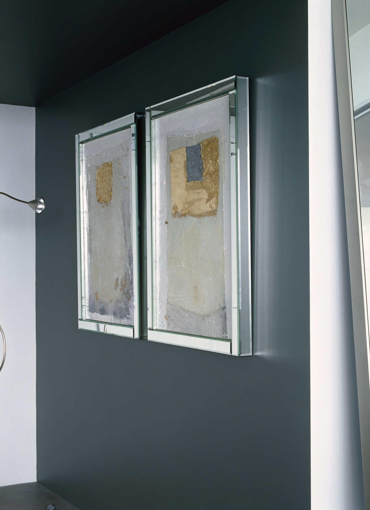 View of two side by side paintings against door, glass, window, gray, black
