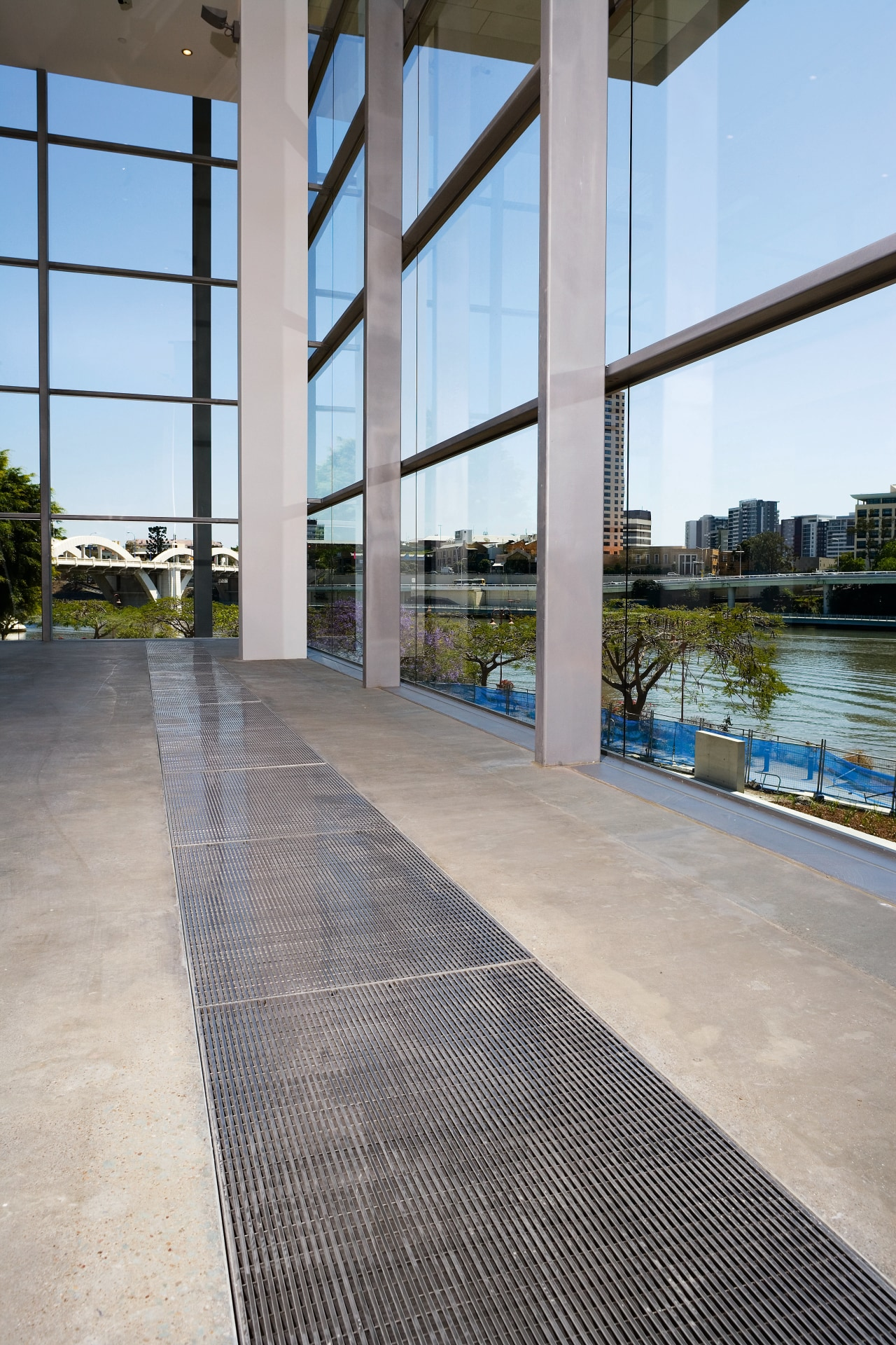 A viewof some polished concrete flooring by ACO apartment, architecture, building, condominium, floor, flooring, real estate, reflection, sky, walkway, water, window, gray
