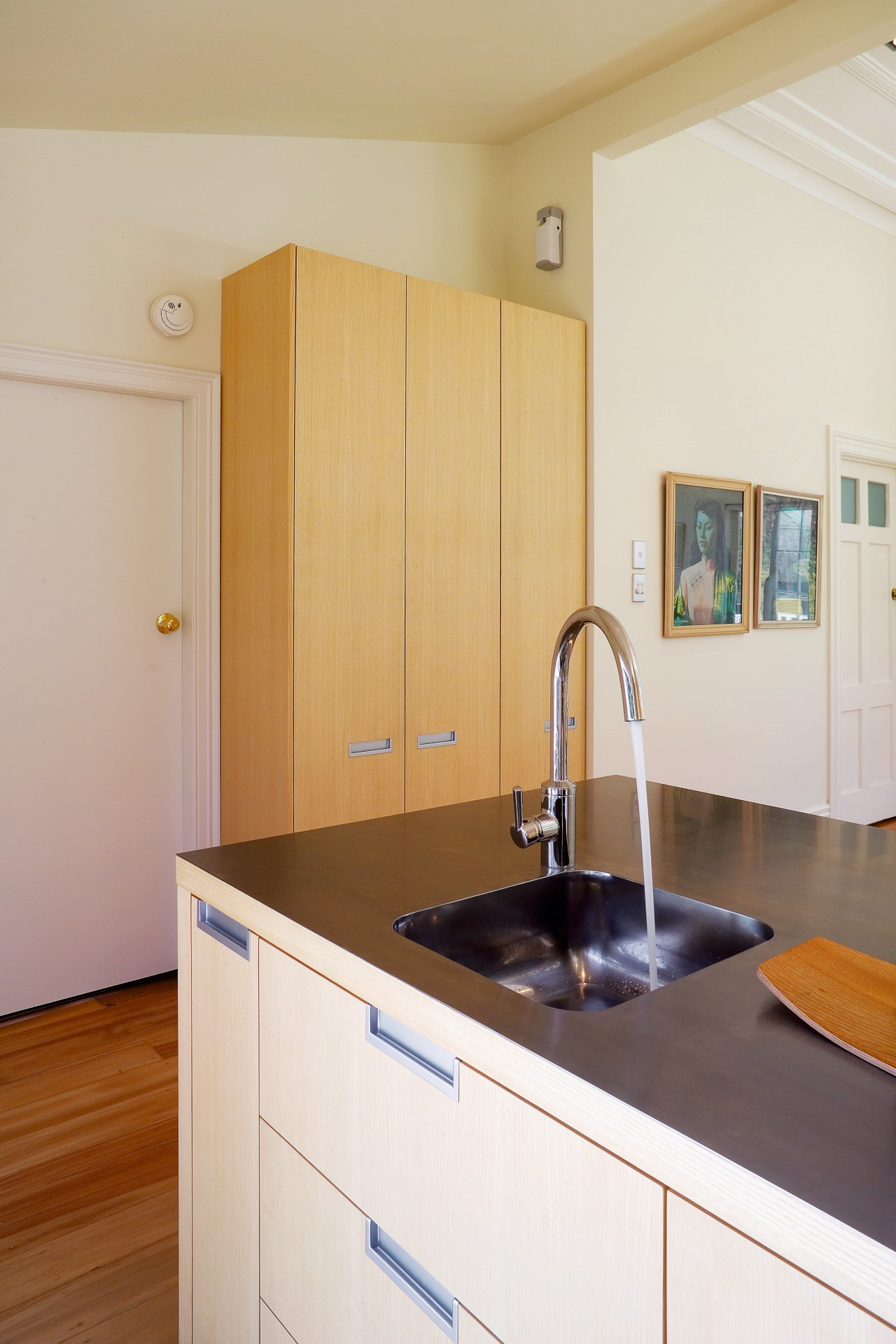 A close up view of the kitchen sink. cabinetry, countertop, floor, interior design, kitchen, real estate, room, sink, white, orange