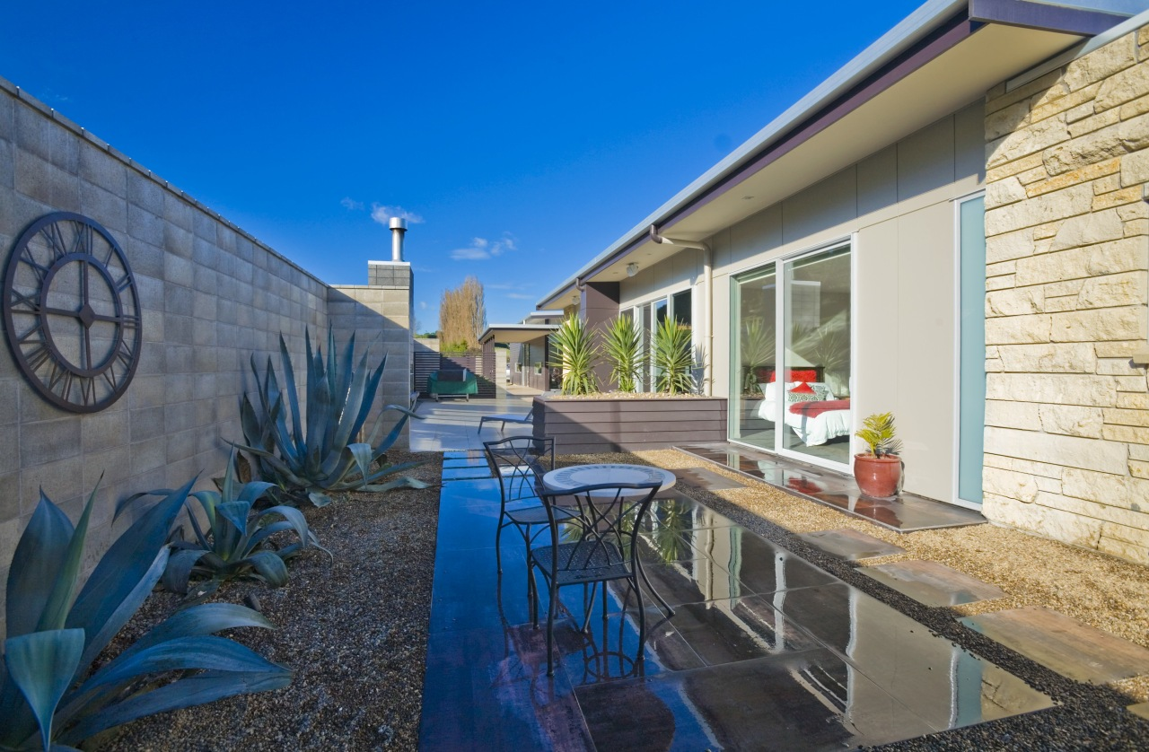 An exterior view of the patio area, concrete apartment, cottage, estate, home, house, property, real estate, villa, blue