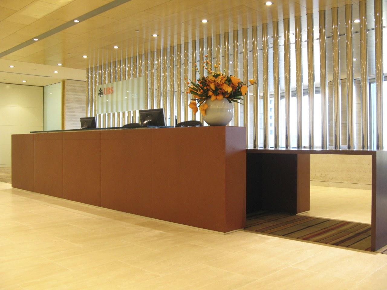 The leather and wenge veneer reception desk reflects floor, flooring, furniture, hardwood, interior design, lobby, wall, orange, brown