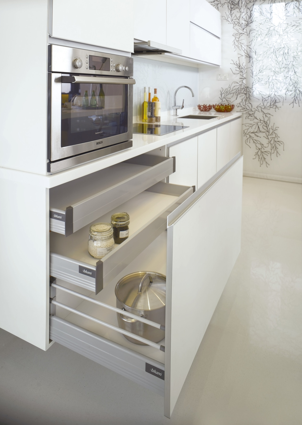 The sleek cabinetry features a white laminate with countertop, drawer, furniture, home appliance, kitchen, kitchen appliance, kitchen stove, major appliance, product, product design, gray, white