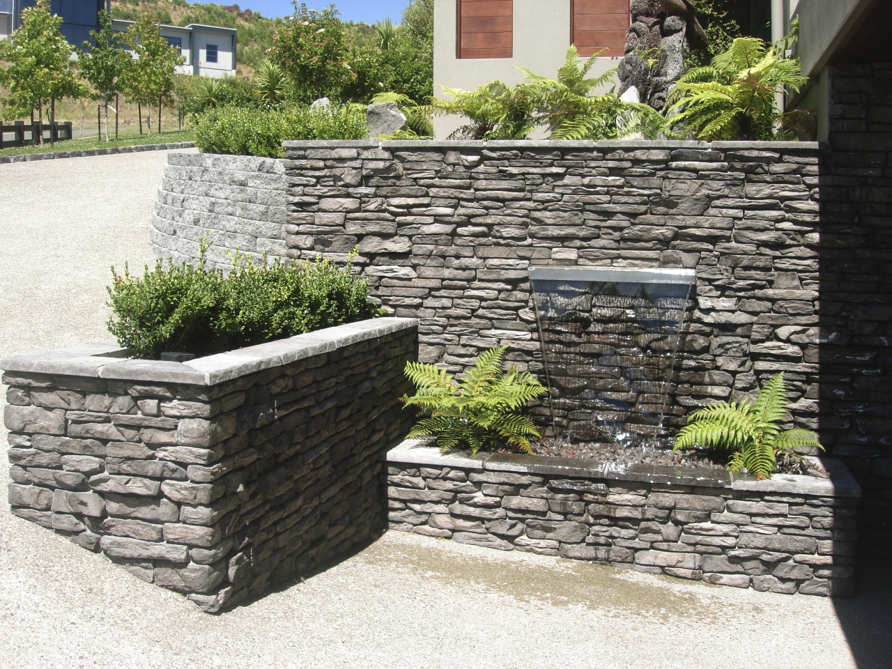 View of garden which includes a stone wall stone wall, walkway, wall, white