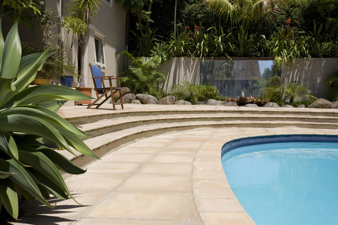 View of a pool with paving that features arecales, backyard, landscaping, leisure, outdoor structure, plant, real estate, swimming pool, walkway, water, yard, brown, orange