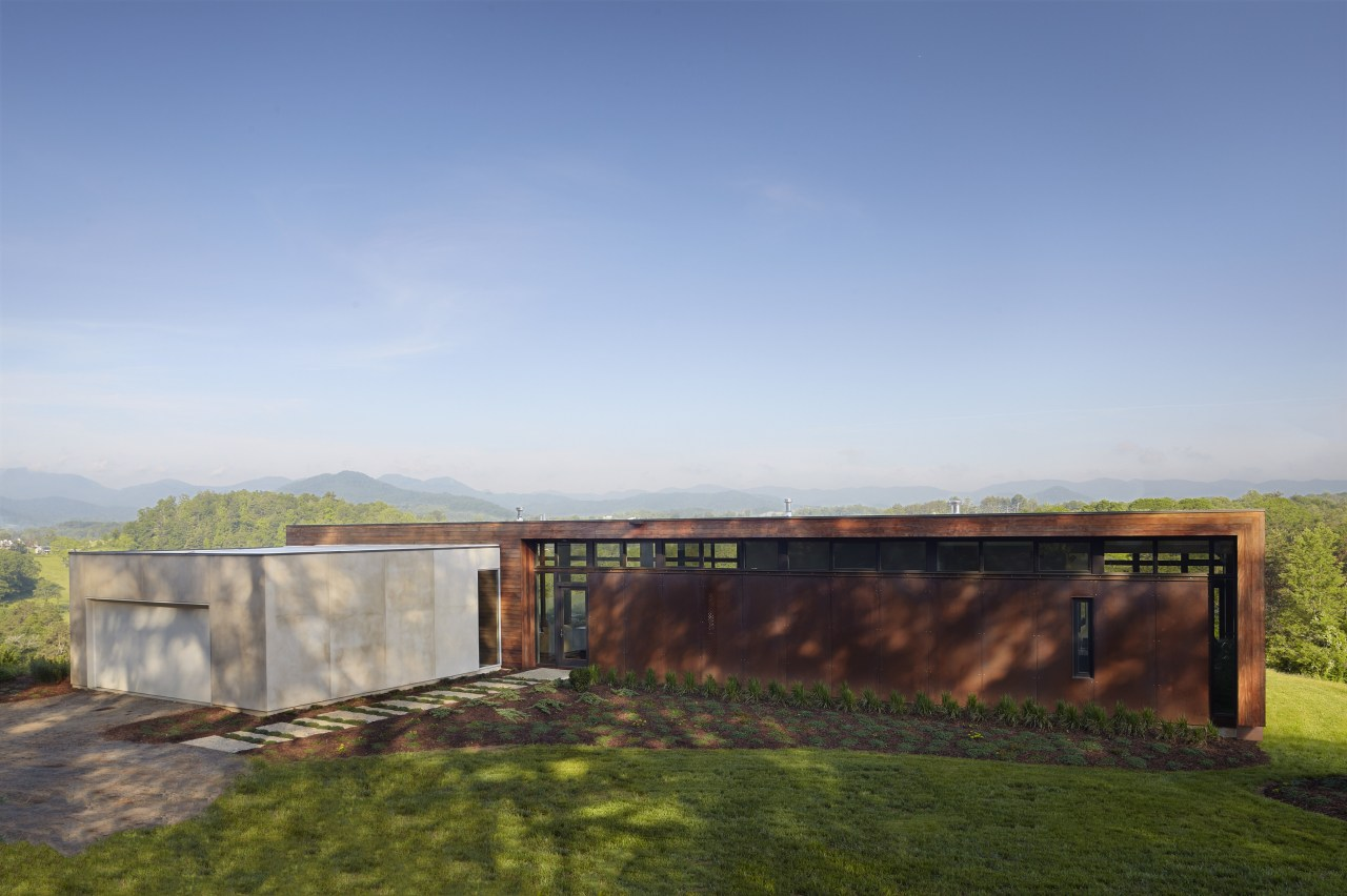 Exterior of house with rusted corten steel. Sustainable architecture, cloud, estate, grass, home, horizon, house, land lot, landscape, property, real estate, rural area, sky, sunlight, teal