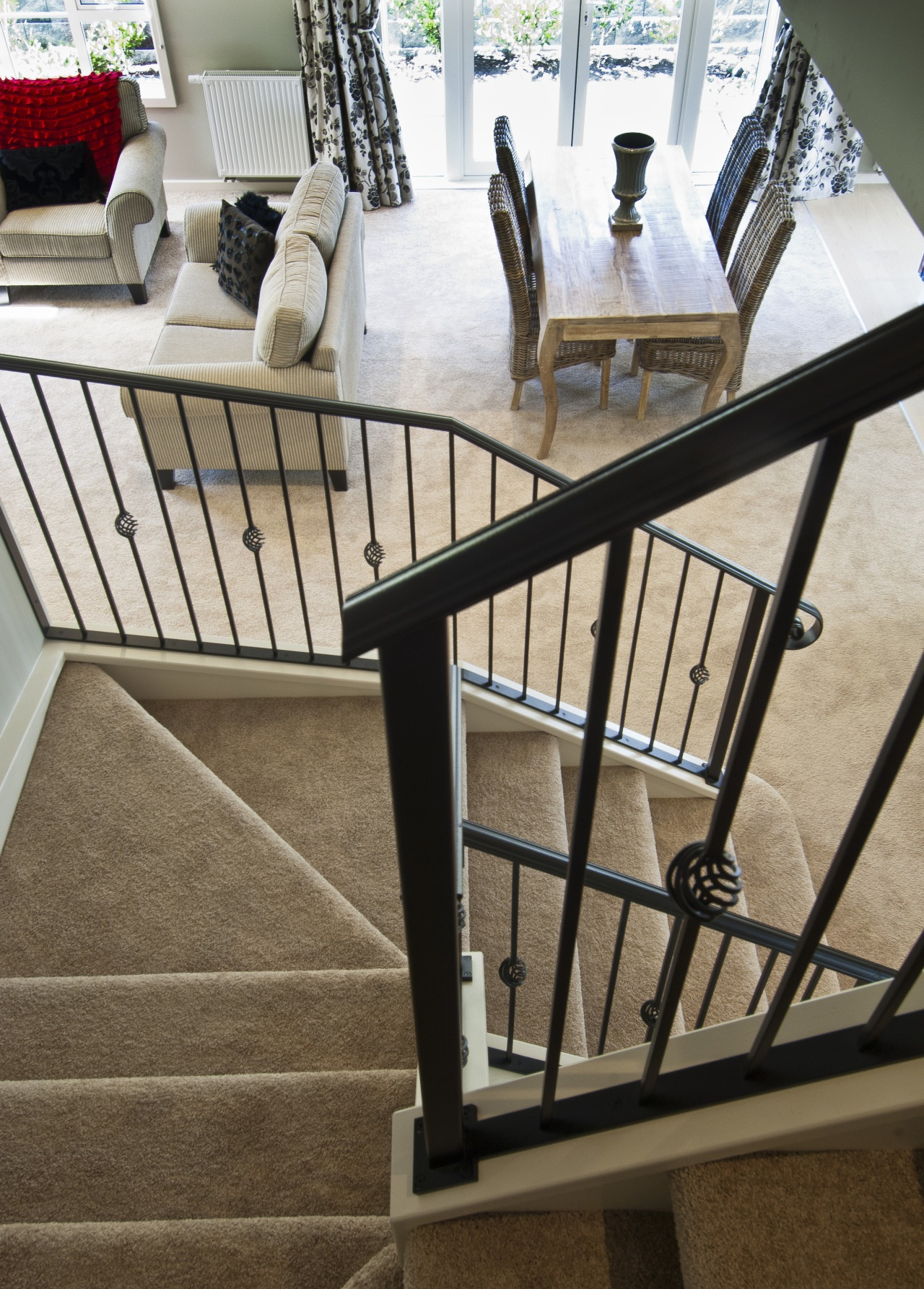 wrought iron banister carpeted stairs leading to lounge baluster, chair, floor, flooring, furniture, handrail, iron, product, stairs, table, brown, white